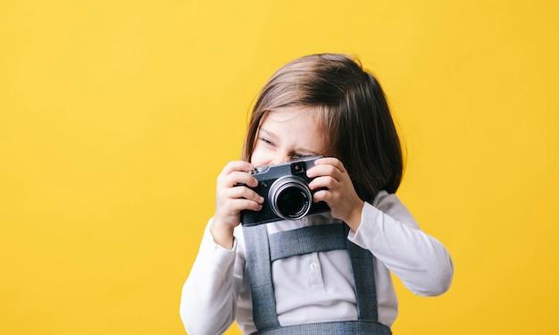 Ragazza che usando una macchina fotografica sulla parete gialla