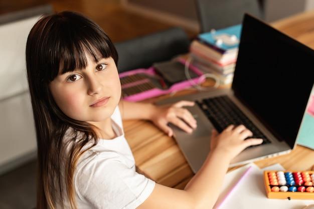 Ragazza che utilizza computer portatile, studiando attraverso il sistema di e-learning online.