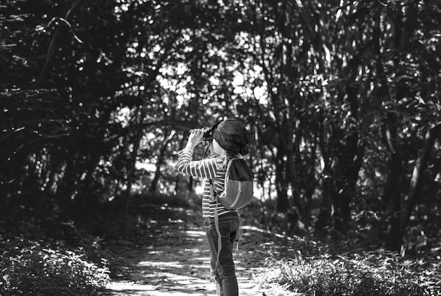Ragazza che utilizza il binocolo nella foresta