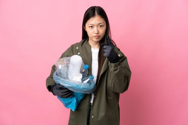 Ragazza cinese che giudica una borsa piena di bottiglie di plastica da riciclare sul rosa isolato frustrato e che indica la parte anteriore