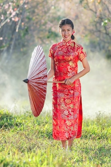 Ragazza cinese con abito tradizionale cheongsam in giardino