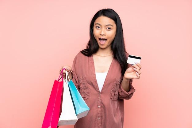 Ragazza cinese dell'adolescente isolata sui sacchetti della spesa rosa della tenuta della parete e sorpresa