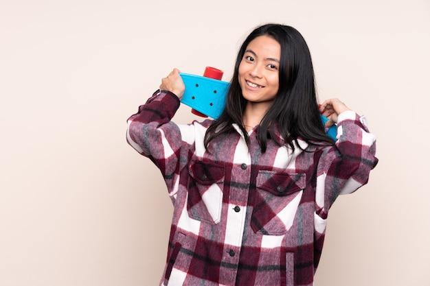 Ragazza cinese dell'adolescente isolata sul beige con un pattino con l'espressione felice