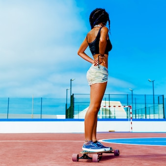 Ragazza colombiana su longboard. freedom street fashion