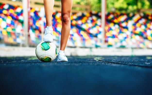 Ragazza con allenamento palla sullo stadio