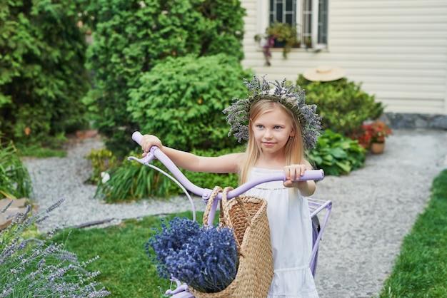 Ragazza con bici e lavanda in estate nel cortile