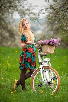 Ragazza con bicicletta bianca vintage con cesto di fiori