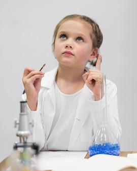 Ragazza con camice da laboratorio e microscopio