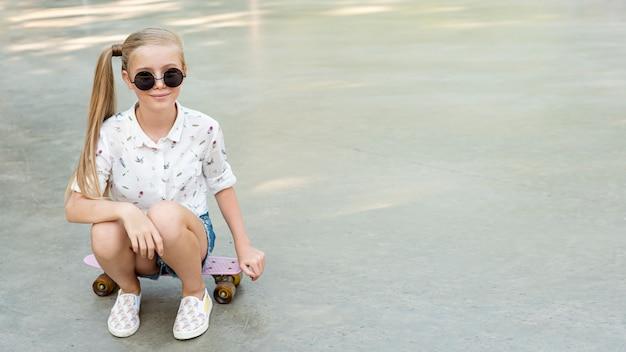 Ragazza con camicia bianca seduto su skateboard