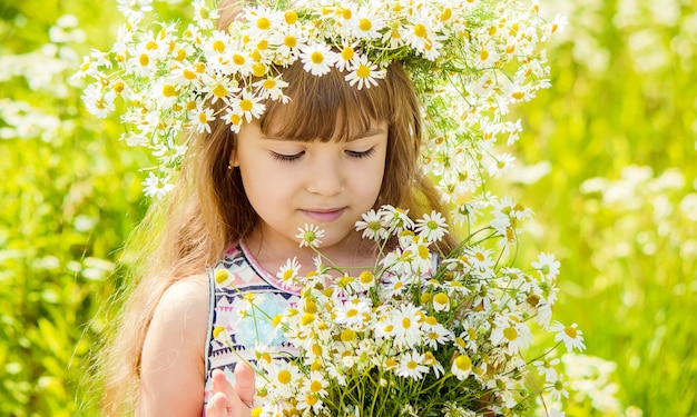 Ragazza con camomilla messa a fuoco selettiva i fiori della natura
