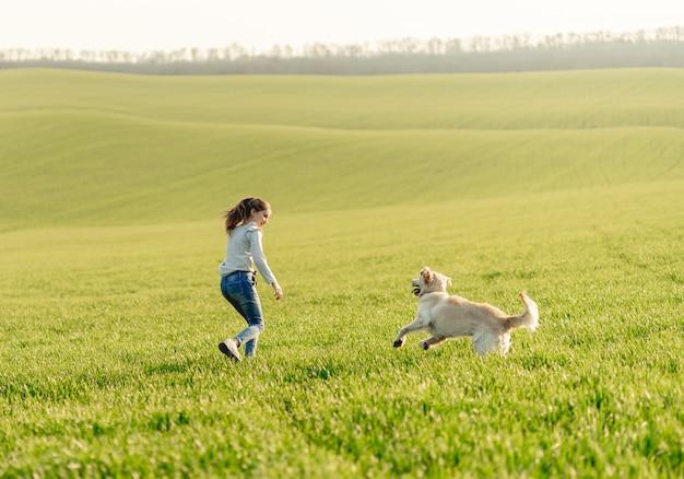 Ragazza con cane sul campo soleggiato