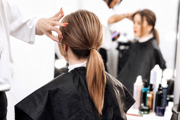 Ragazza con capelli lunghi castani con un'acconciatura di coda
