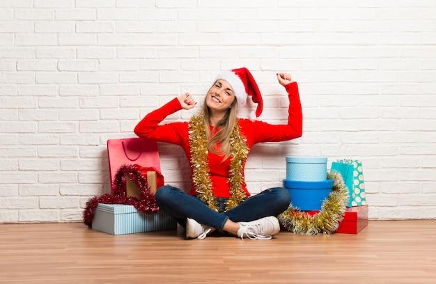 Ragazza con cappello di natale e molti regali che celebrano le vacanze di natale ascoltando il