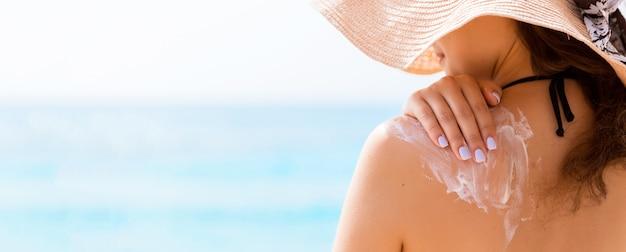 Ragazza con cappello di paglia sta applicando la protezione solare