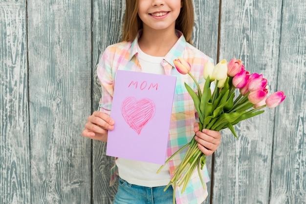 Ragazza con cartolina e fiore sorridente