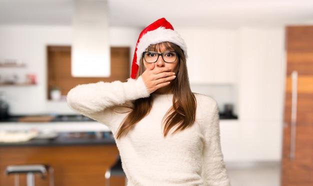 Ragazza con celebrando le vacanze di natale che copre la bocca con le mani