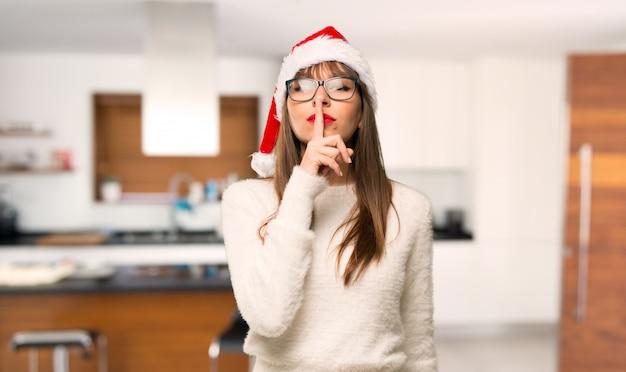 Ragazza con celebrando le vacanze di natale mostrando un segno di silenzio gesto