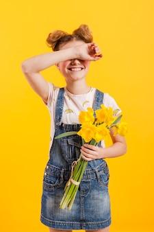 Ragazza con fiori che coprono gli occhi