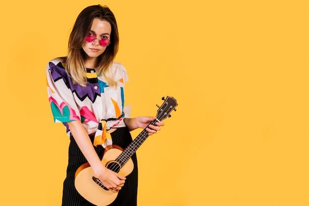 Ragazza con gli occhiali a suonare il ukelele