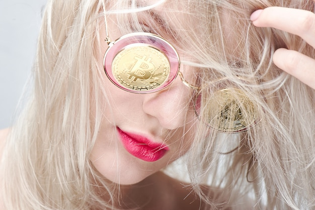 Ragazza con gli occhiali con bitcoin su sfondo bianco