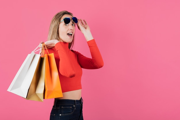 Ragazza con gli occhiali da sole che tengono i sacchetti della spesa