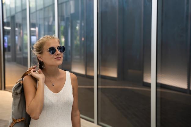 Ragazza con gli occhiali da sole che tiene una borsa con la mano sulla schiena in piedi davanti a un edificio moderno e guardando il cielo
