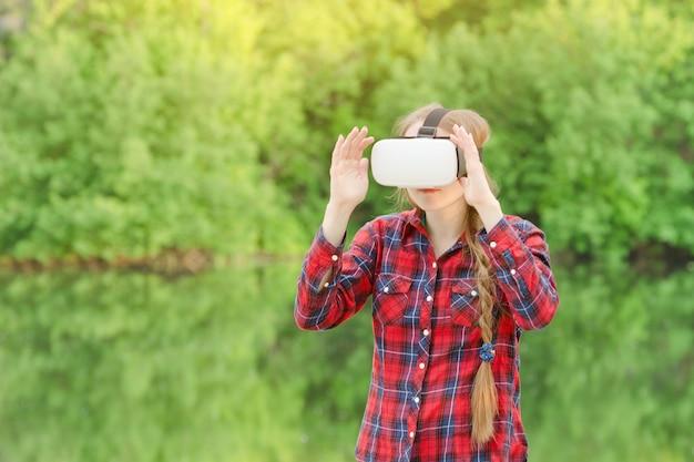 Ragazza con gli occhiali di realtà virtuale. vegetazione di sfondo