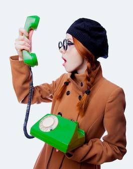 Ragazza con gli occhiali e il cappotto che parla dal telefono
