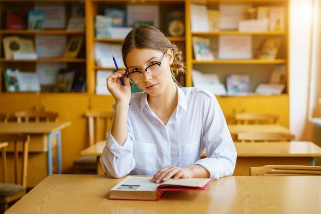 Ragazza con gli occhiali seduto a un tavolo con un libro in classe