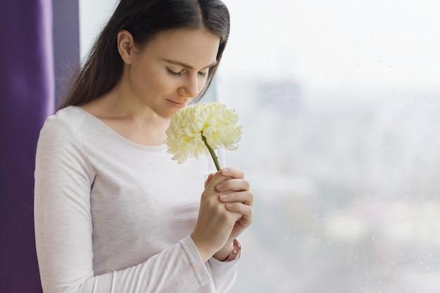 Ragazza con grande fiore giallo pallido vicino alla finestra