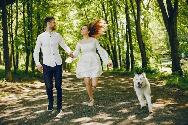 Ragazza con i capelli chiari vestita in abito bianco sta giocando con il suo cane e il suo fidanzato