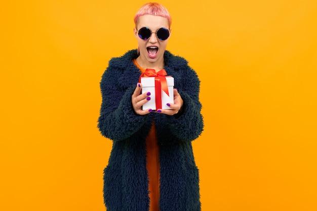Ragazza con i capelli rosa con un piercing al naso e la lingua vestita con una pelliccia e occhiali in possesso di un regalo su uno sfondo giallo