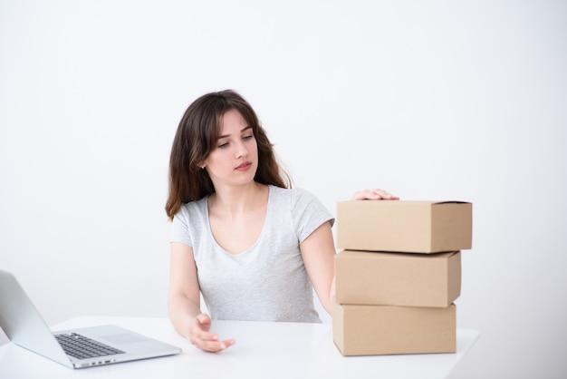 Ragazza con i capelli, una maglietta grigia seduto a un computer portatile e guardando una pila di scatole di cartone. servizio di consegna online