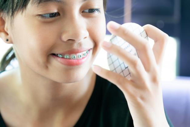 Ragazza con i denti delle parentesi graffe che guardano allo specchio che pulisce i suoi denti