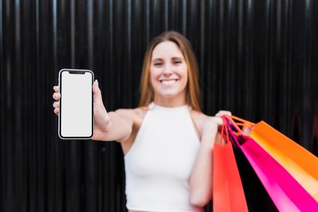 Ragazza con i sacchetti della spesa che tengono il modello del telefono