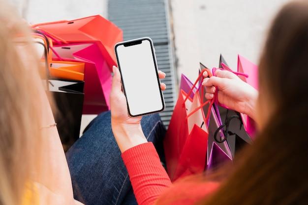 Ragazza con i sacchetti della spesa che tiene telefono