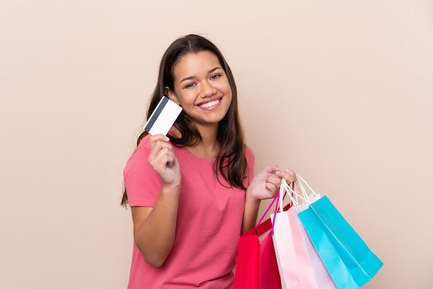 Ragazza con i sacchetti della spesa della tenuta del sacchetto della spesa e una carta di credito
