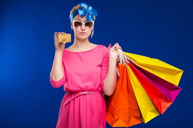 Ragazza con i sacchetti e la carta di credito in mani