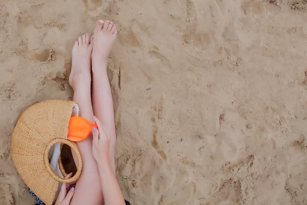 Ragazza con i suoi elementi essenziali per la spiaggia per una vacanza estiva