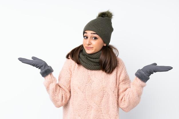 Ragazza con il cappello di inverno che ha dubbi con l'espressione confusa del fronte