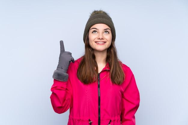 Ragazza con il cappello di inverno isolato sull'azzurro che indica su e sorpreso