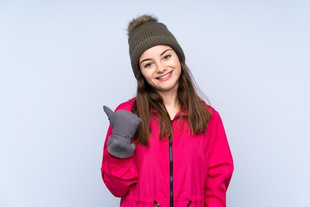 Ragazza con il cappello di inverno sulla parete blu che indica il lato per presentare un prodotto