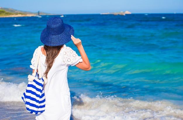 Ragazza con il cappello di paglia e la borsa a strisce blu alla spiaggia tropicale