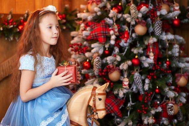 Ragazza con il contenitore di regalo vicino all'albero di natale