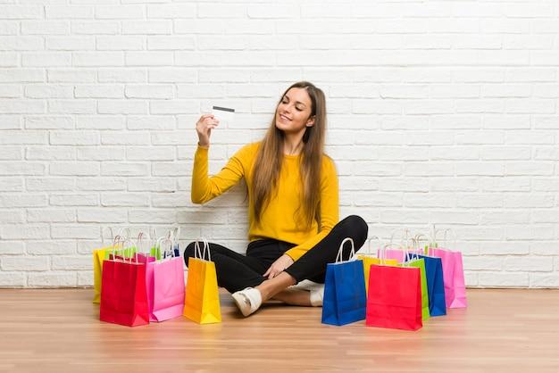 Ragazza con il lotto dei sacchetti della spesa che tiene una carta di credito e un pensiero