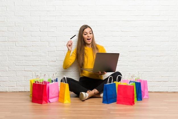 Ragazza con il lotto dei sacchetti della spesa con il computer portatile e la carta di credito