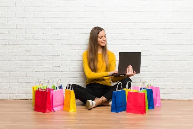 Ragazza con il lotto dei sacchetti della spesa con il computer portatile