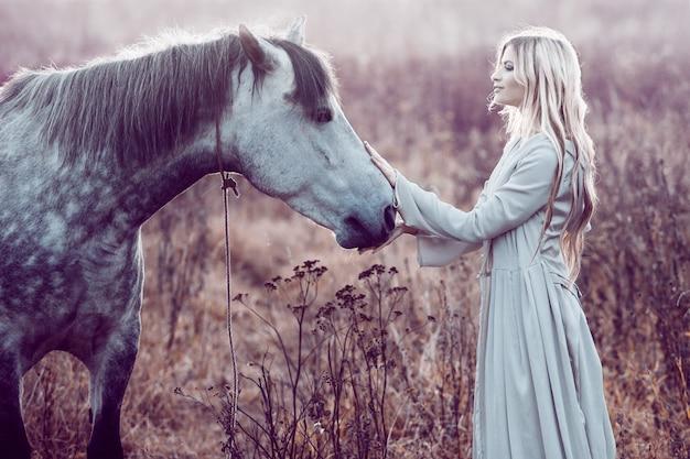 Ragazza con il mantello con cappuccio con cavallo, effetto di tonificazione