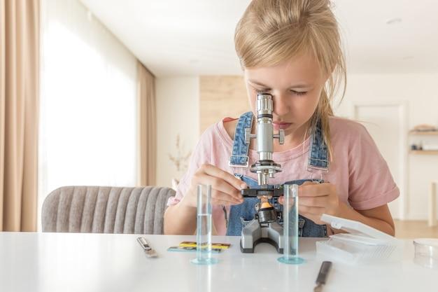 Ragazza con il microscopio a casa che impara chimica e gioco