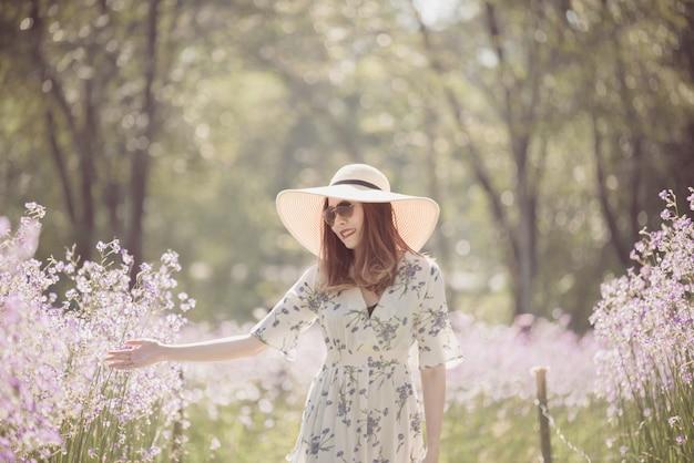 Ragazza con il suo cappello di paglia in un campo di fiori, donna felice godendo in campo di fiori